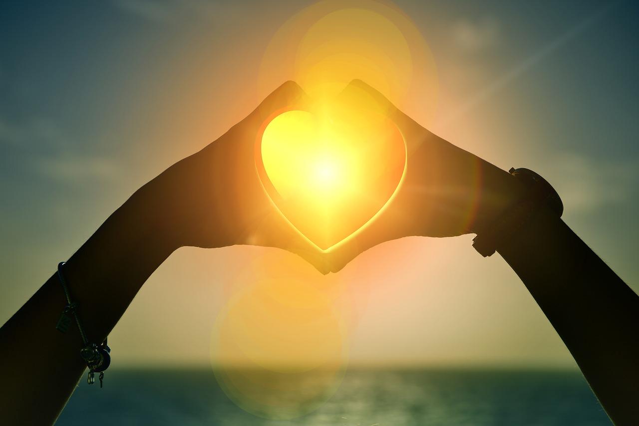 2 Hände formen ein Herz vor einem Sonnenuntergang
